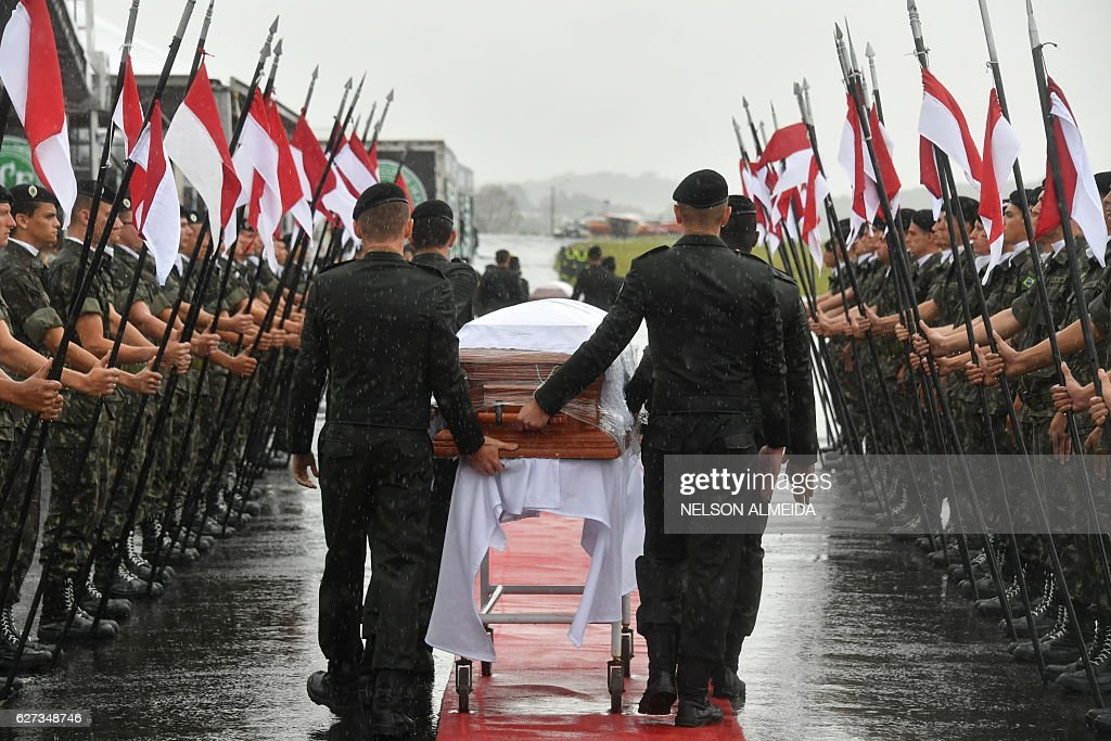 TOPSHOT - A military guard of honor receives the coffins of the members of the Chapecoense Real football club team killed in a plane crash in Colombia, upon their arrival at the airport of Chapeco, in Santa Catarina, southern Brazil, on December 3, 2016. The first of two Brazilian air force planes carrying the remains of a football team killed in a plane crash arrived Saturday in the city of Chapeco in southern Brazil. / AFP / Nelson Almeida