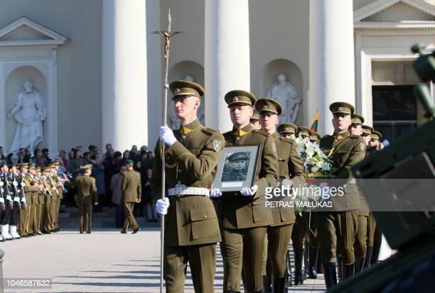 Military guards hold a portrait of the commander of the 19441953 partisan resistance movement against Soviet occupation Adolfas Ramanauskas during a...