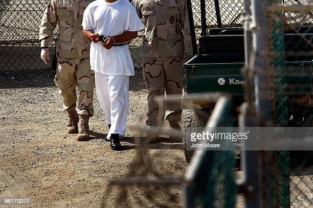US military guards walk a detainee through Camp Delta in the Guantanamo Bay detention center on March 29 2010 in Guantanamo Bay Cuba US President...