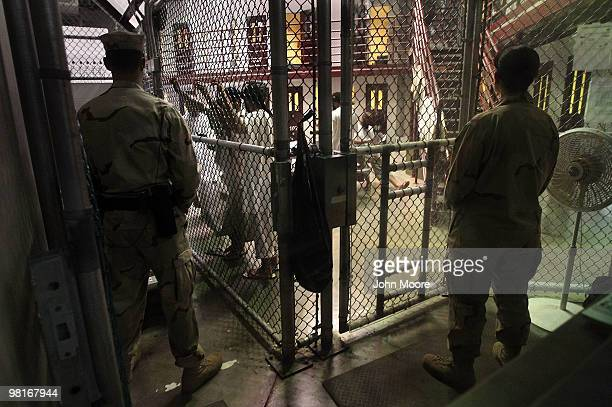 Military guards watch detainees in a cell block at Camp 6 in the Guantanamo Bay detention center on March 30, 2010 in Guantanamo Bay, Cuba. U.S....