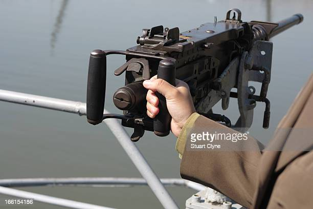 CONTENT] A military guide holds a machine gun on the captured American spy ship the USS Pueblo on the Taedong River in Pyongyang