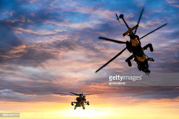 military gunships flying against dramatic sky at sunset - apache helicopter stock pictures, royalty-free photos & images