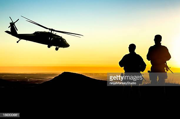 military helicopter and army soldiers overlook the setting sun - military helicopter stock photos and pictures