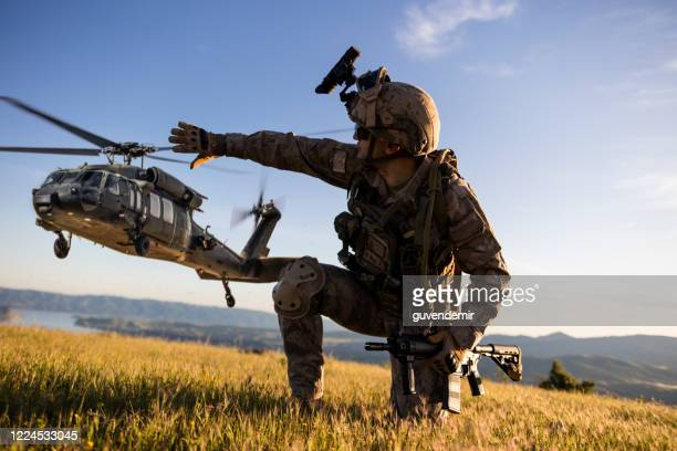 military helicopter approaching behind the kneeling army soldier - nato stock pictures, royalty-free photos & images