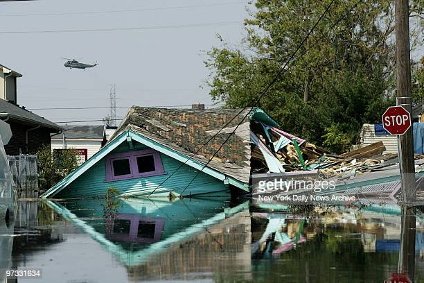 Military helicopter buzzes over the splintered remains of a house in the flooded Ninth Ward neighborhood of New Orleans, La., in a search for...