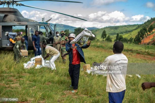TOPSHOT A military helicopter delivers food aid for the survivors of the Cyclone Idai in Chimanimani on March 20 2019 International aid agencies...