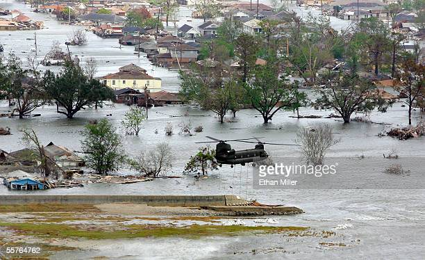 Military helicopter drops bags of sand onto the breach in the repaired Industrial Canal levee next to homes in the Lower Ninth Ward September 24,...