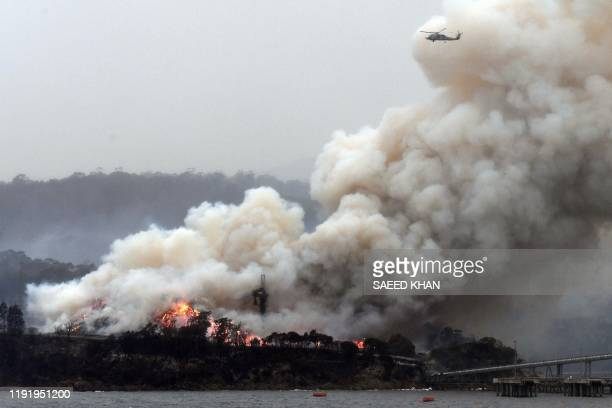 TOPSHOT A military helicopter flies above a burning woodchip mill in Eden in Australia's New South Wales state on January 6 2020 January 5 brought...
