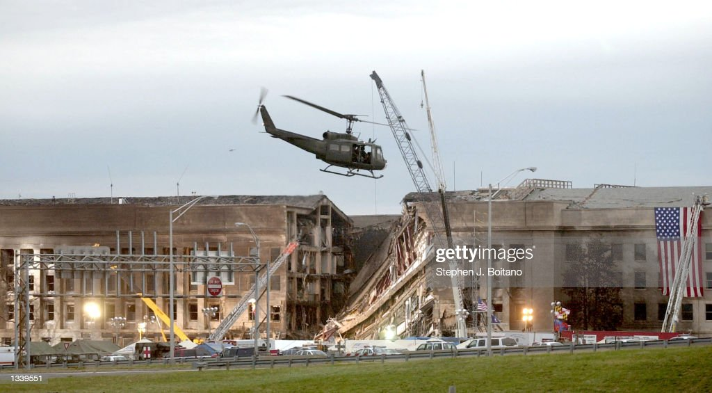 A military helicopter flies in front of the Pentagon September 14, 2001 in Arlington, Virginia at the impact site where a hijacked airliner crashed into the building.