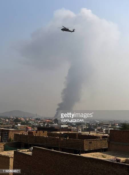 Military helicopter flies near the site of a massive explosion the night before near the Green Village in Kabul on September 3, 2019. - A massive...