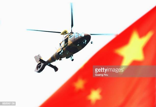 A military helicopter flies over a Chinese national flag on July 8 2009 in Urumqi the capital of Xinjiang Uighur autonomous region China Ethnic riots...