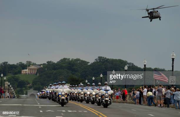 A military helicopter flies over a police escort in the beginning of the Rolling Thunder annual motorcycle rally in Washington DC May 28 2017...