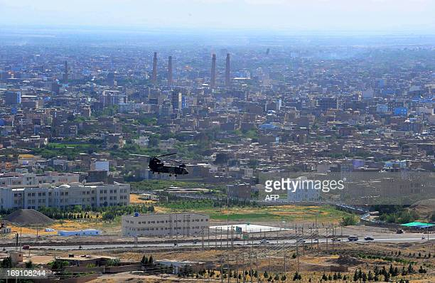 A military helicopter flies over Herat city during an official a meeting between Herat and European Union officials in Herat on May 19 2013 A group...