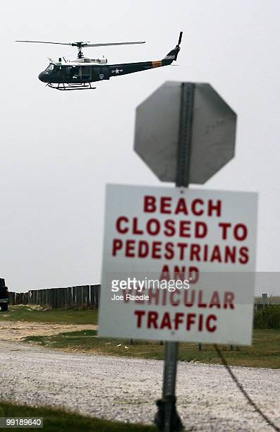 A military helicopter flies past a beach closed sign after what appeared to be small oil globs washed ashore at Fourchon Beach as efforts continue to...