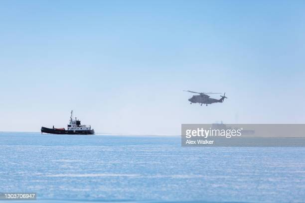 military helicopter hovering low next to ships. - heatwave stock pictures, royalty-free photos & images