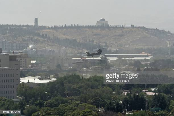 Military helicopter is pictured flying above the US embassy in Kabul on August 15, 2021. Several hundred employees of the US embassy in Kabul have...