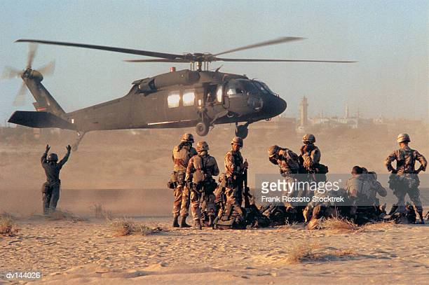 Military helicopter landing in desert as group of soldiers watching
