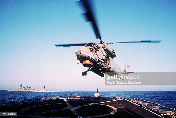 Military Helicopter landing on deck of aircraft carrier