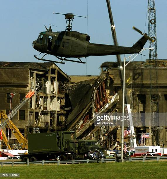 A military helicopter lands on the South side of the Pentagon as a truck moves material out from the wreckage of hijacked American Airlines Flight 77...