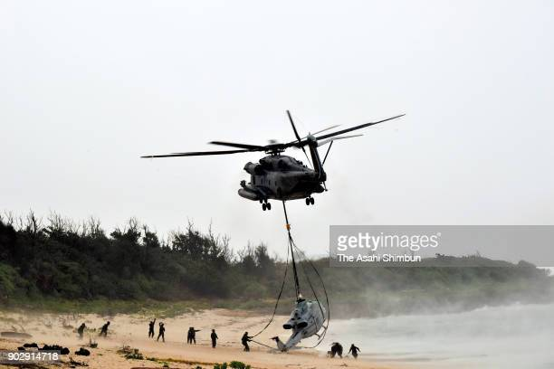 A US military helicopter lifts the crippled UH1 utility helicopter from a beach on Ikeijima island two days after it made an emergency landing on...