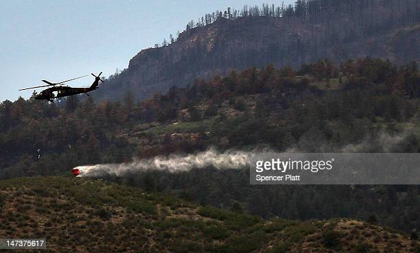 A military helicopter with a water bucket participating in fire containment flies over part of the Waldo Canyon fire on June 28 2012 in Colorado...