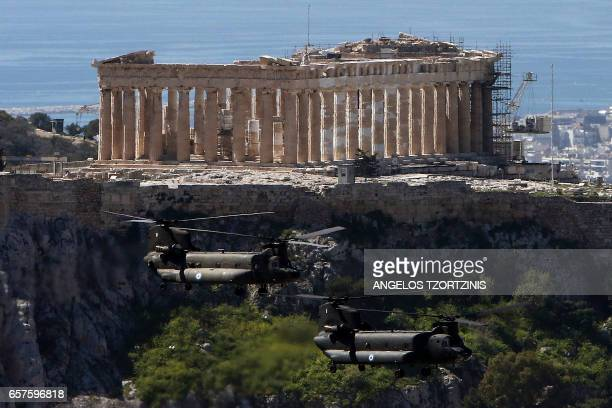 Military helicopters fly over the Parthenon at the Acropolis on March 25, 2017 in Athens, during a military parade marking Greece's Independence Day....