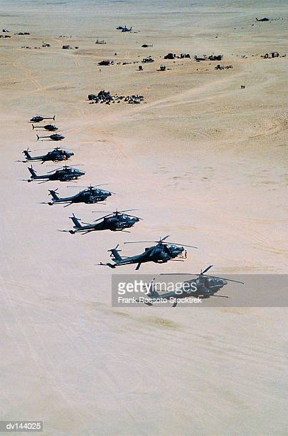 military helicopters in flight over base camp - military helicopter stock photos and pictures