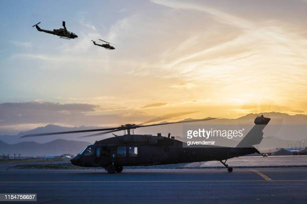 military helicopters on airbase at sunset - base stock pictures, royalty-free photos & images