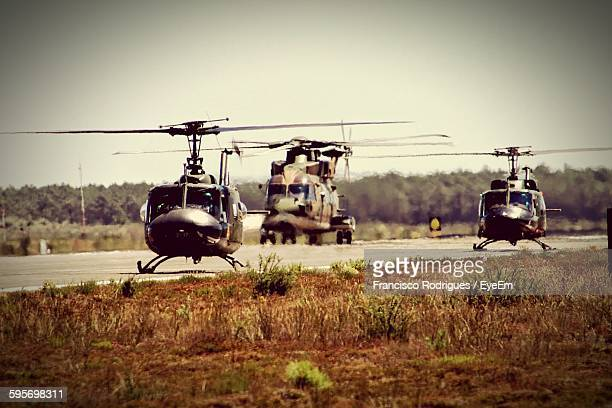 Military Helicopters On Army Base Against Sky