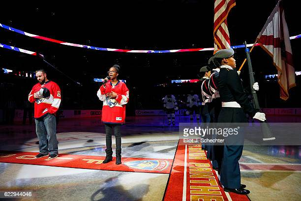 Military Hero and US Army Veteran William Marshall stands on the ice for the national anthem while it is sung by High School student Taylor Sawyer...