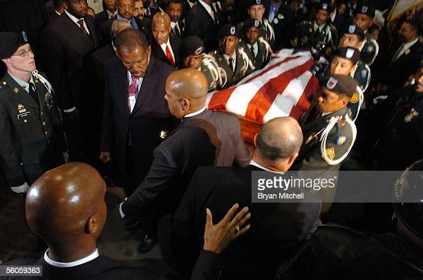 A military honor guard carries the casket containing civil rights pioneer Rosa Parks out of Greater Grace Temple as Jesse Jackson and Detroit Mayor...