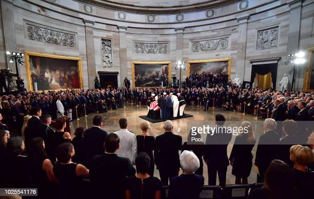 A military honor guard carries the casket of former Senator John McCain into the Capitol Rotunda where he will lie in state at the US Capitol in...