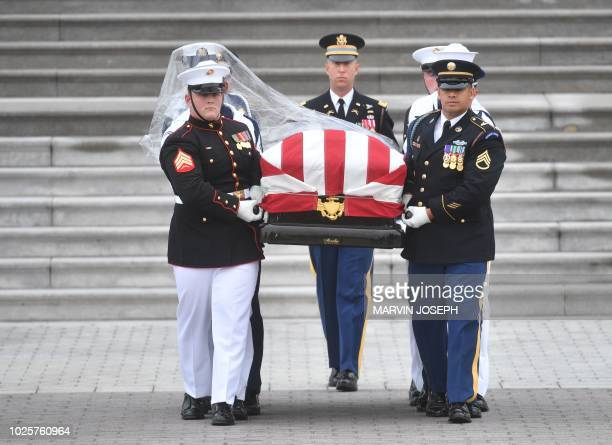 A Military Honor Guard carries the casket of US Senator John McCain from the US Capitol in Washington DC on September 1 2018 McCain's remains will be...