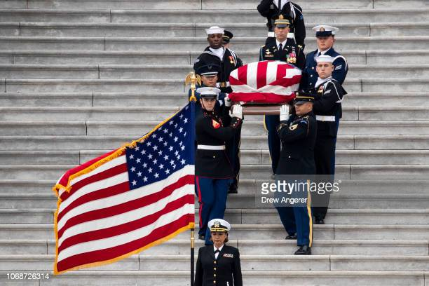 S military honor guard carries the flagdraped casket of the late former President George HW Bush down the steps of the US Capitol December 5 2018 in...