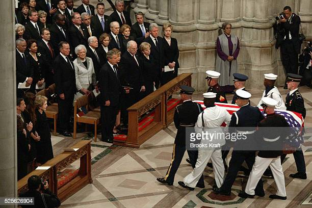 A military honor guard carry the casket of former US President Ronald Reagan after his state funeral at the National Cathedral in Washington At lower...
