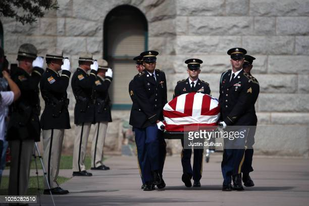 A military honor guard carry the casket of US Sen John McCain from the Arizona State Capitol to go to a memorial service at the North Phoenix Baptist...