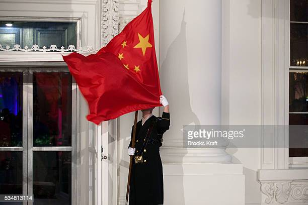 Military honor guard holds the Chinese flag in front of the White House in Washington. Chinese President Hu Jintao was at the White House for a state...