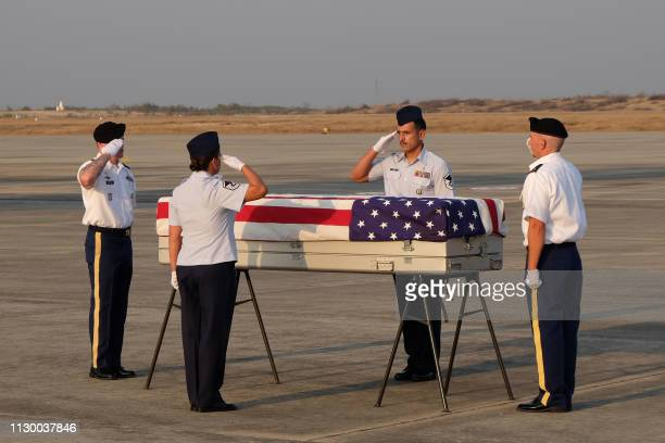 Military honor guards salute over the flag draped coffin bearing the recovered remains of suspected American airmen during a repatriation ceremony at...