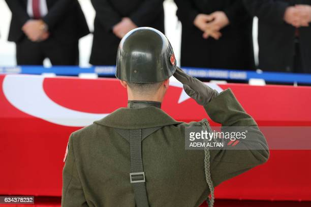 A military honour guard salutes in front of the coffin of Mahmut Uslu one of five Turkish soldiers killed on Ferbuary 7 in an attack by IS militants...