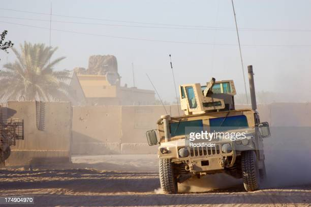 Military humvee driving through desert like conditions