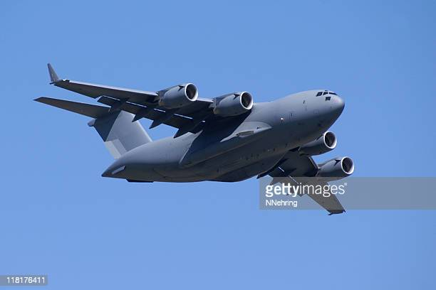 military jet cargo airplane C17 Globemaster flying in blue sky