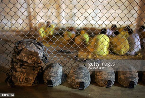 US military kevlar helmets sit in a row along a fence beside Iraqi detainees inside the Camp Bucca detention centre located near the KuwaitIraq...