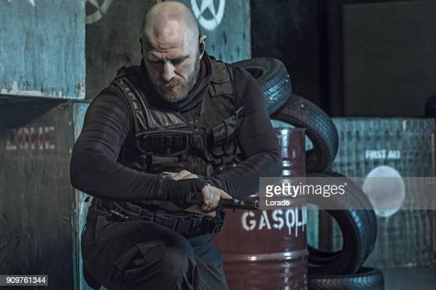 Military Krav Maga fighting group member of swat team posing in dark indoor urban setting
