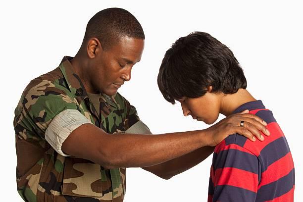 A Military Man Praying For A Teenage Boy