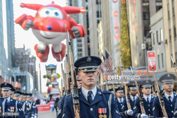 Military members march ahead of the Jett balloon on 6th Ave during the annual Macy's Thanksgiving Day parade on November 23 2017 in New York City The...