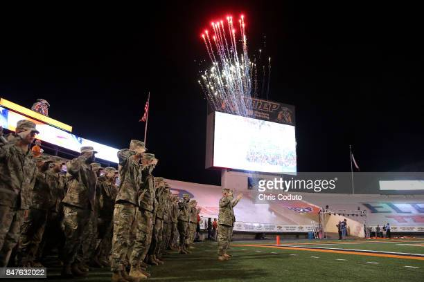 Military members salute during the National Anthem before the start of the college football game between the UTEP Miners and the Arizona Wildcats at...