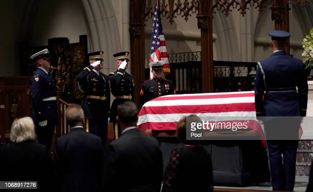 Military members salute the flagdraped coffin of former President George HW Bush as it lies in repose at St Martin's Episcopal Church on December 5...