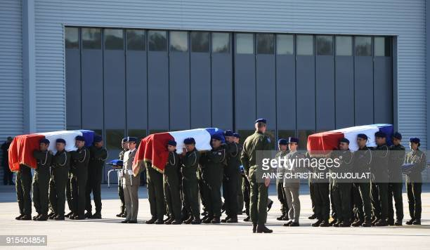 Military men carry the victim's caskets during a national tribute ceremony to five helicopter pilot officers killed after two army helicopters...