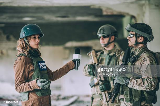 hombres militares dando entrevista desde la zona de guerra - reportaje imágenes fotografías e imágenes de stock