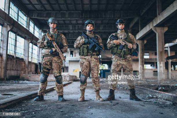 military men standing in abandoned warehouse - task force stock pictures, royalty-free photos & images